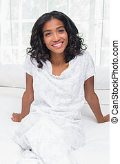 Pretty woman smiling at camera sitting on bed
