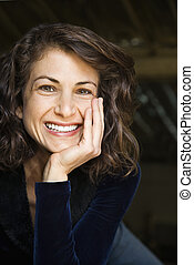 Portrait of pretty mid adult Caucasian woman smiling with head on hand making eye contact.