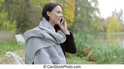 Pretty woman speaking on phone in park - Pretty woman in...
