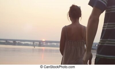 Pretty woman standing on the beach, watching sun going down, back to the girl comes a man gives her flowers and charming couple in love hugging enjoying at sunset in slowmotion. 1920x1080