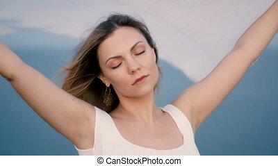 Pretty woman stands on cliff over sea and holds long white fabric veil, like sails fluttering in wind. Concept of femininity, tenderness, freedom. High quality 4k footage