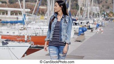 Pretty woman strolling on a waterfront promenade -...