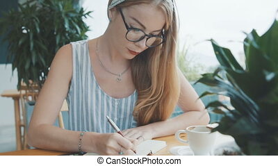 Pretty woman studying and writing in notebook. Female sitting at table in cosy cafe.
