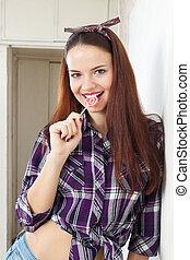 Pretty woman sucking lollipop in home