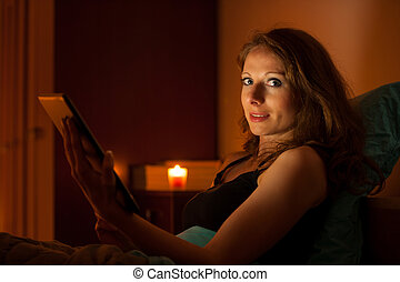 Pretty woman surfing web on a tablet in bed before sleeping