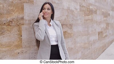 Pretty woman talking on phone and leaning on wall