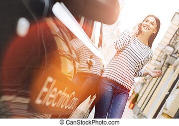 Pretty woman talking on the phone near electric car