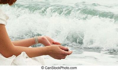 Pretty Woman Throwing Pebbles Into Black Sea Sitting on Beach