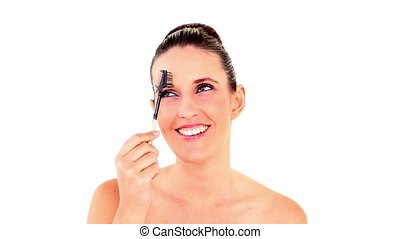 Pretty woman tidying her eyebrows on white background