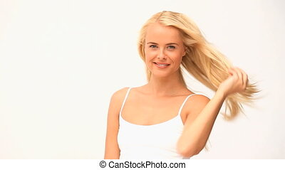 Pretty woman tidying her hair against a white background