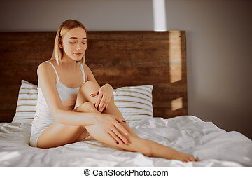 people, beauty, depilation, epilation and body care concept - beautiful woman with bare legs sitting on bed at home, beautification conc