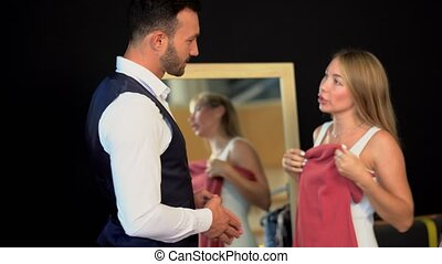 Pretty woman tries a new dress in dressing room.