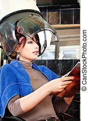 Pretty woman under bonnet hair dryer - Pretty lady reading a...