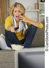 pretty woman upset about watching tv