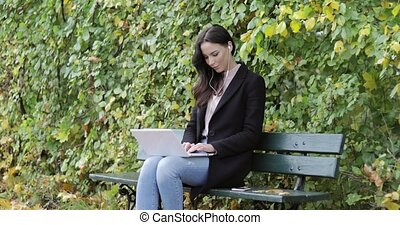 Pretty woman using laptop in park