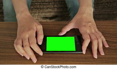 Pretty woman using smart phone with green screen display