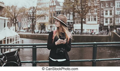 Pretty woman using smartphone on a bridge. 4K. Young lady in...