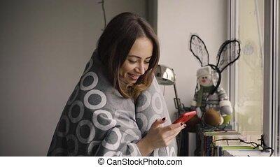 Pretty woman using smartphone standing by window , blanket