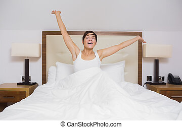 Pretty woman waking up in hotel room and stretching