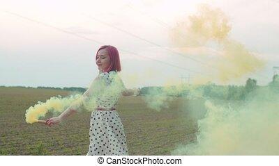 Pretty woman walking in color smoke across field - Close-up...