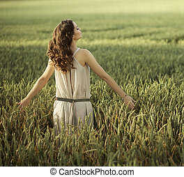 Attractive woman walking on the corn field