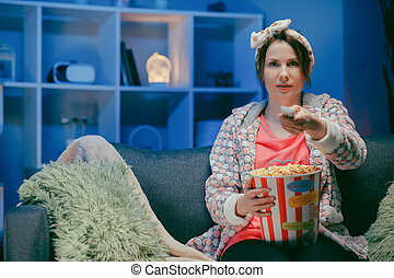 Pretty woman watching something funny on tv at home. Eating popcorn