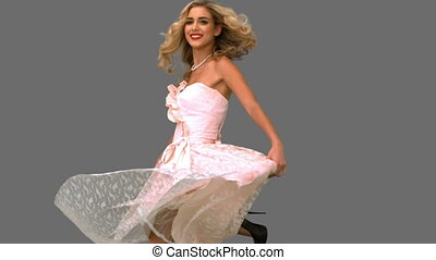 Pretty woman wearing a gown revolving on grey screen in slow...