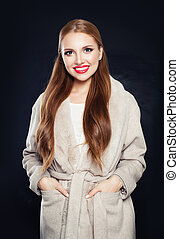 Pretty woman wearing coat on black background