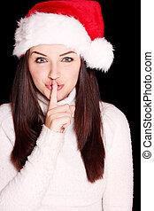 Pretty woman wearing santa hat saying shh