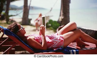 Pretty woman wearing sunglasses working on laptop in a beach chair. 1920x1080