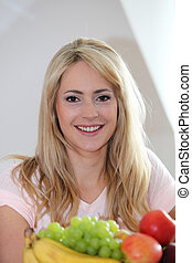 Pretty woman with a dish of fresh fruit