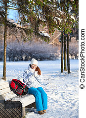 Pretty woman with backpack sitting on a bench in winter park