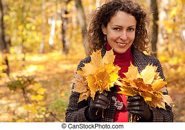 Pretty woman with bouquets of maple leaves in autumnal park