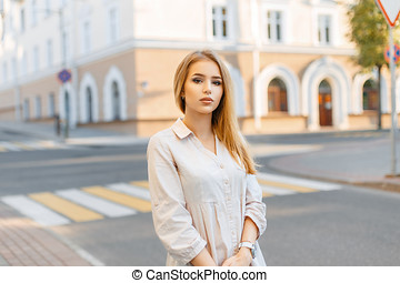 Pretty woman with brown eyes posing on a background of the city.