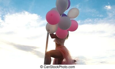 Pretty woman with bunch of balloons performs a pole-dance,...