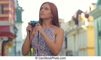 Pretty woman with camera in the city