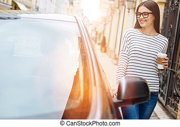 Pretty woman with coffee cup touching her car