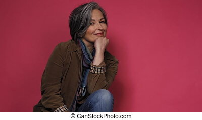 Pretty woman with gray hair smiling on camera with hand on ...