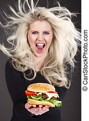 pretty woman with hamburger laughs and screams