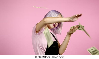 Pretty woman with happy face scatters, waste money. Hipster girl with violet dyed hair overspend US. Lady is flush with dollars on pink studio background. High quality 4k footage