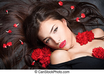 woman with long hair and red carnations