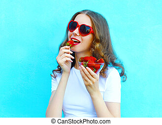 Pretty woman with many strawberry over colorful blue background
