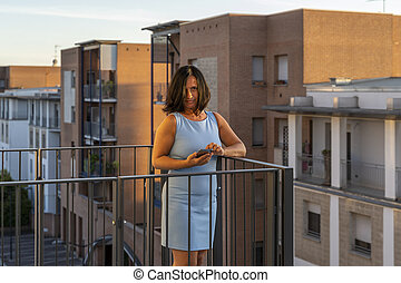 pretty woman with mask standing on terrace during quarantine due to coronavirus pandemic.