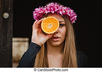 Pretty woman with pink wreath of flowers and a orange
