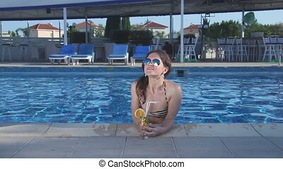 """Pretty woman with sexy body in bikini drinking cocktail in pool"""