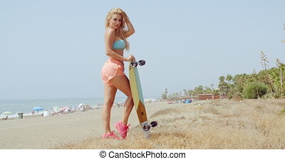 Pretty Woman with Skateboard Posing at the Beach