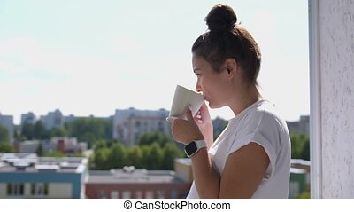 Pretty woman with smart watch standing on balcony looking out over city drinking a cup of tea or coffee