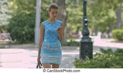 Pretty woman with smartphone walking in the city