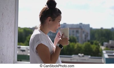 Pretty woman with smartwatch standing on balcony looking out over city drinking a cup of tea or coffee