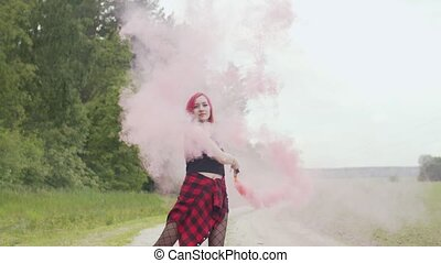Pretty woman with smoke bomb dancing on dusty road - Stylish...